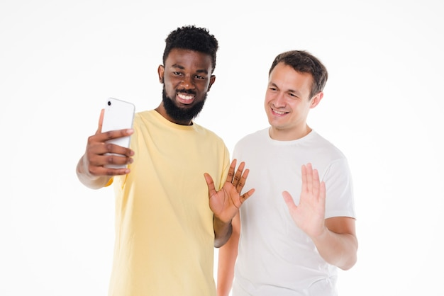 Twee mannen van gemengd ras die selfie met smartphonecamera nemen die op witte muur wordt geïsoleerd