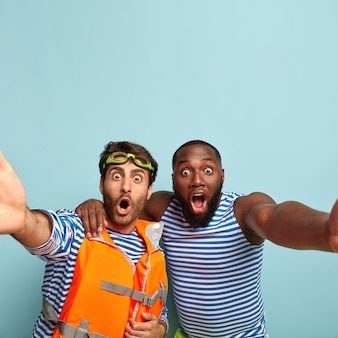 Twee mannen van gemengd ras staren met geschokte uitdrukkingen, maken een selfie-portret, omhelzen elkaar, houden hun mond open, brengen vrije tijd door aan zee