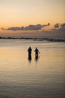 Twee mannen vissen in de oceaan vanaf het strand bij zonsondergang