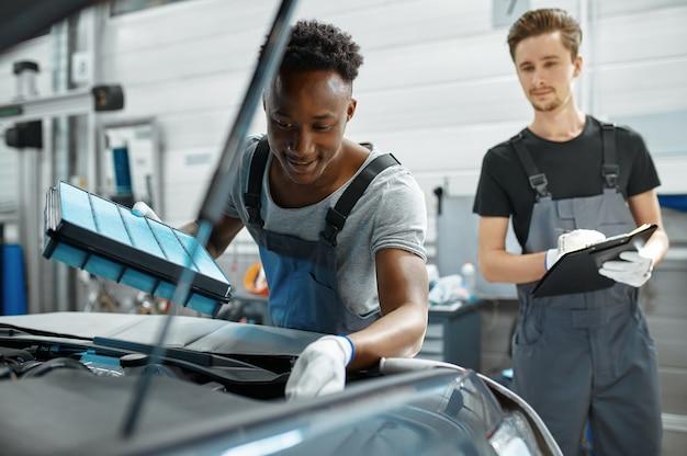 Twee mannen werknemers repareert motor in mechanische werkplaats.
