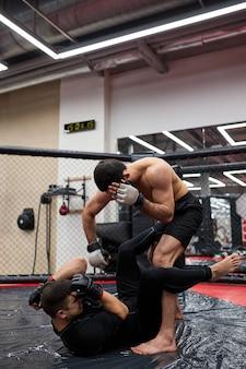 Twee mannen worstelaars van worstelen maakt onderwerping worstelen. oefen vechttechnieken, vechten op de vloer in de sportschool, samen trainen, trainen