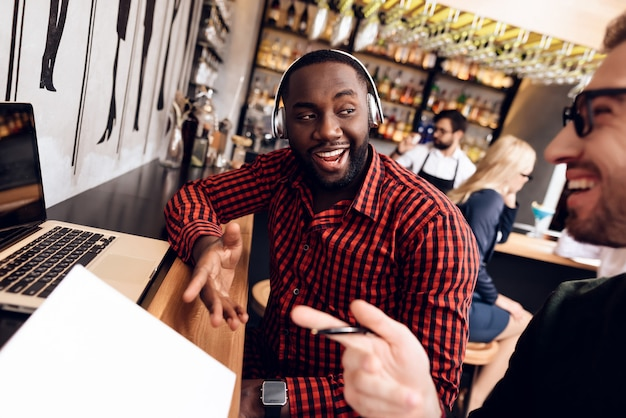 Twee mannen zitten aan de bar met een computer.