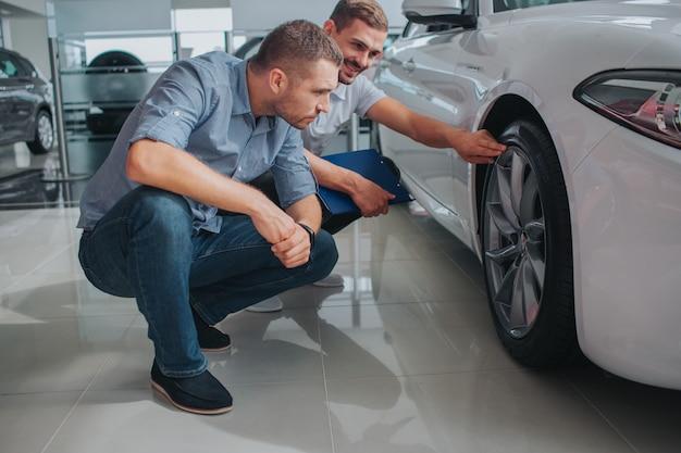 Twee mannen zitten in squad positie en kijken naar het wiel van witte auto. berded man wijst bovenop het wiel. hij kijkt naar een andere man en glimlacht. ernstige man kijkt ook. hij is geconcentreerd.