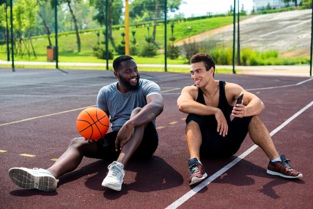Twee mannen zitten op het basketbalveld