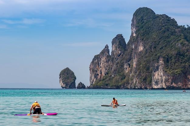 Twee mans kajakken op de andamanzee in de buurt van tropische phi phi-eilanden. zonnige dag en aquamarijnwater.