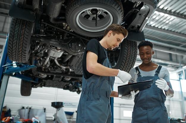 Twee mechanische mannen op zoek op controlelijst in mechanische werkplaats.