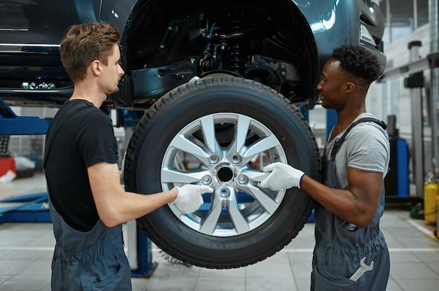 Twee mechanische mannen tot vaststelling van wiel in mechanische werkplaats.