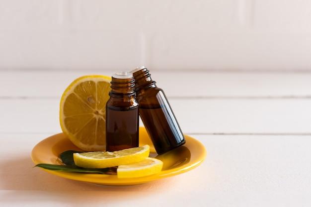 Twee medische flessen met een druppel met essentiële citrusolie op een gele keramische tprel tegen een achtergrond van citroen en een witte bakstenen muur.