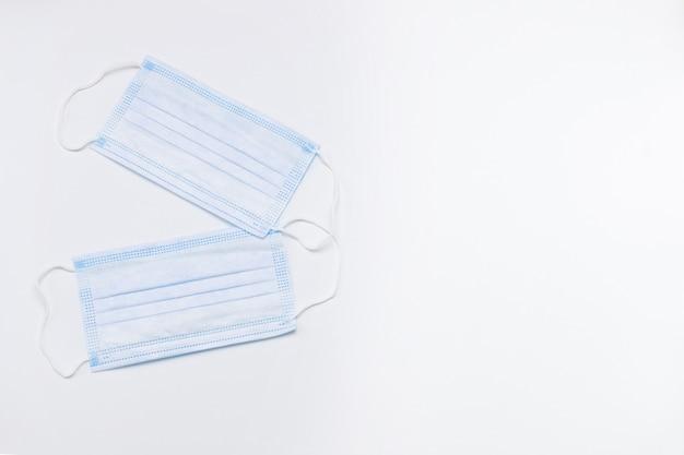 Twee medische wegwerpmaskers op een witte achtergrond