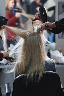 Twee meesters tegelijkertijd gedroogd met haardrogers haar blonde model in schoonheidssalon. achteraanzicht.