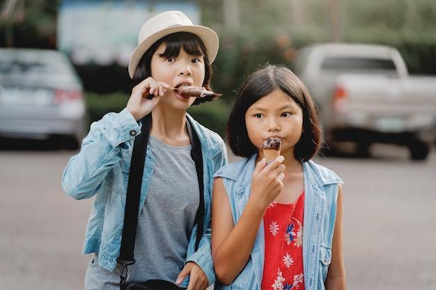 Twee meisje eten van ijs op straat tijdens het wandelen reizen in het park