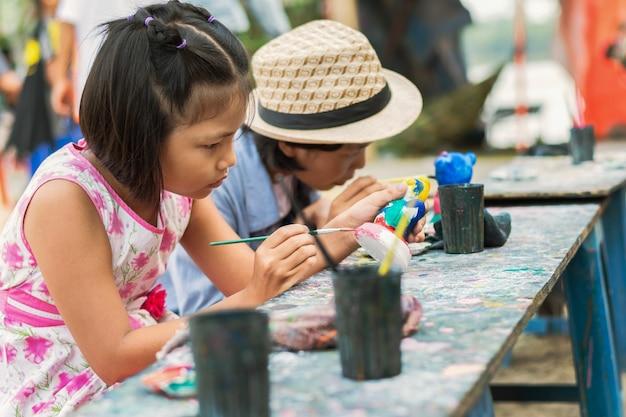 Twee meisje het schilderen pop op houten achtergrond