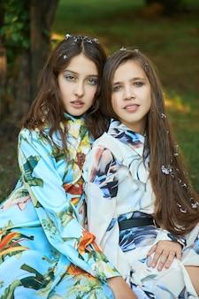 Twee meisje met zich meebrengt in een lila struik in het voorjaar. romantisch portret van een meisjes in bloemen in het zonlicht