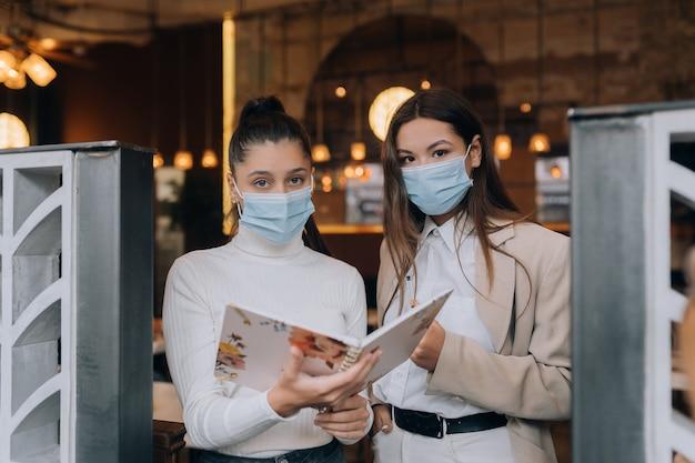 Twee meisjes bij de ingang van het gebouw controleren mensen