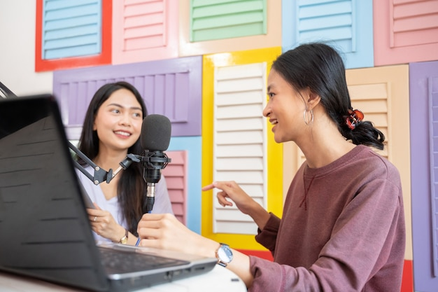 Twee meisjes chatten tijdens podcast met laptop en microfoon