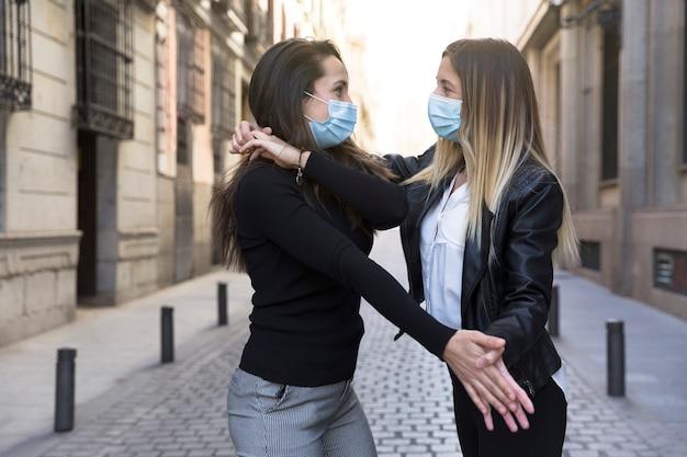 Twee meisjes dansen midden op straat. ze dragen een gezichtsmasker. concept van nieuw normaal.