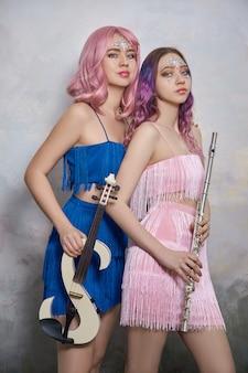 Twee meisjes de muzikant met een viool en een fluit in de handen van de heldere podium kleding.