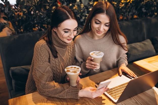 Twee meisjes die aan een computer in een koffie werken