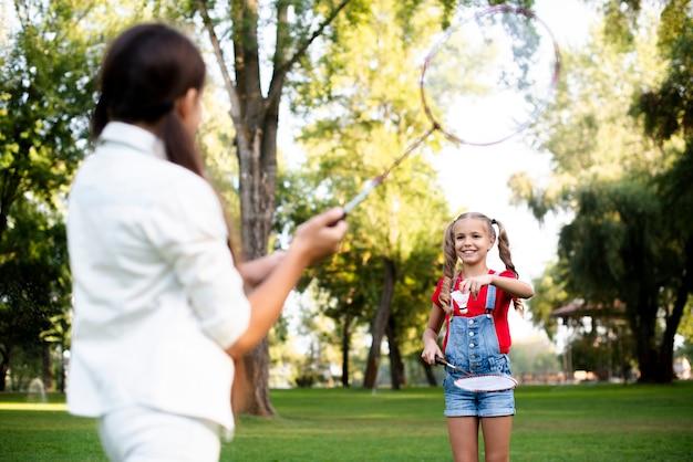 Twee meisjes die badminton op mooie de zomerdag spelen