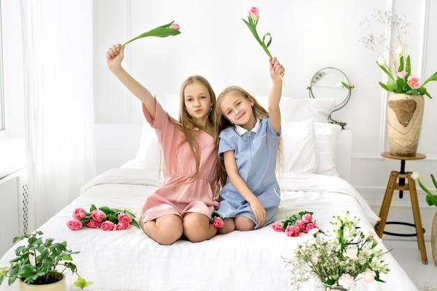 Twee meisjes die gelukkig tulpen zwaaien zittend in bed wereldkinderen dag