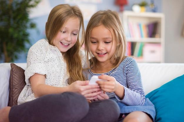 Twee meisjes die grappig bericht van vriend lezen
