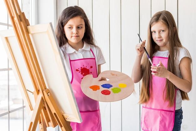 Twee meisjes die het roze schort schilderen samen op schildersezel dragen