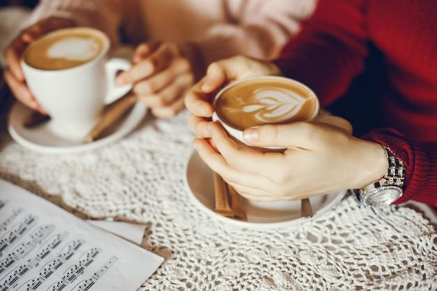 Twee meisjes die koffie hebben terwijl het bestuderen van een muziekscore