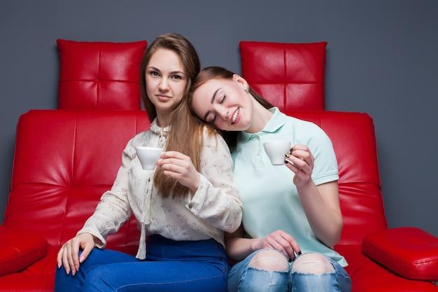 Twee meisjes die met kopjes koffie samen zitten