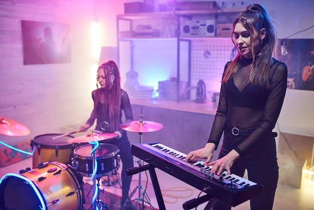 Twee meisjes die muziekinstrumenten bespelen in een geluidsopnamestudio