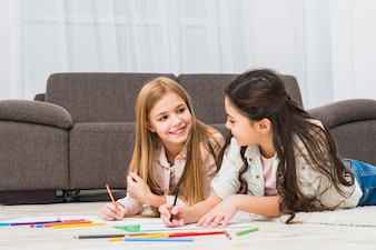 Twee meisjes die op tapijttekening liggen met kleurenpotloden in de woonkamer