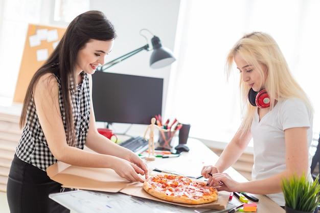 Twee meisjes die pizza op kantoor eten.