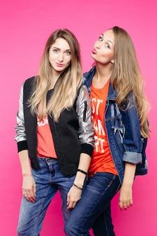 Twee meisjes die pret hebben en bij roze muur stellen.