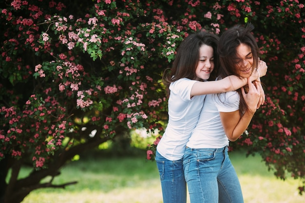 Twee meisjes die soortgelijke kleding dragen die buiten knuffelen