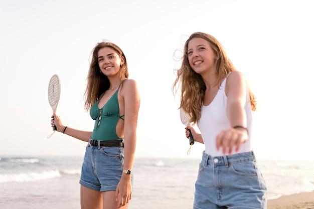 Twee meisjes die strandtennis bij kust spelen