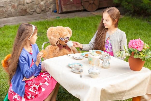 Twee meisjes die theekransje hebben met teddybeer op het erf
