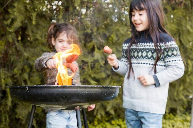 Twee meisjes die worsten bij de brandende barbecue voorbereiden in openlucht