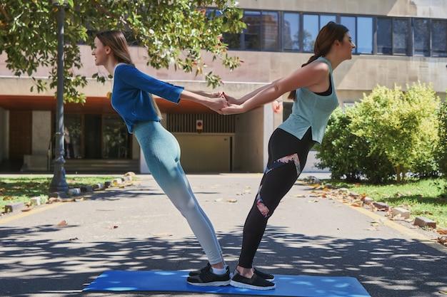 Twee meisjes die yoga-oefeningen doen in de straten van de stad