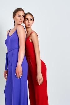 Twee meisjes die zich in studio in elegante kleurrijke overall op witte achtergrond bevinden