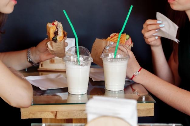 Twee meisjes drinken koude koffie en eten hamburgers in het café