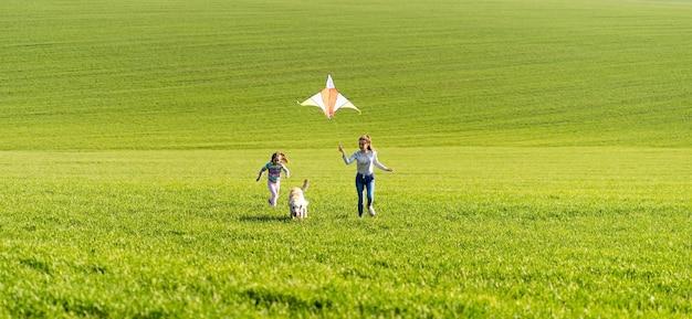 Twee meisjes en een hond rennen op het groene veld en houden een vlieger vast Premium Foto
