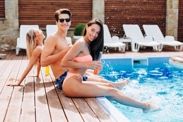Twee meisjes en een man stoppen hun voeten in het water in het zwembad, rusten, hebben plezier