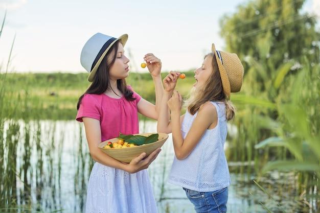 Twee meisjes eten gele kersen in de natuur