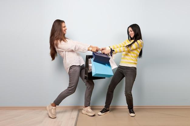 Twee meisjes gekleed in mooie stijlvolle kleding trekken elkaar tassen na het winkelen op de witte achtergrond.