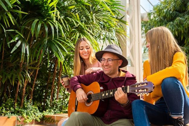Twee meisjes glimlachen terwijl een muzikant gitaar speelt en zingt