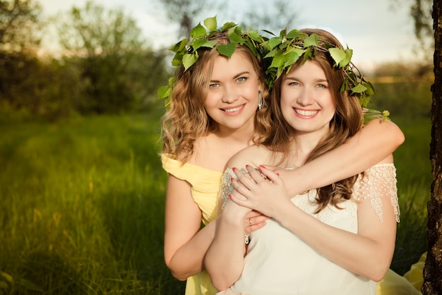 Twee meisjes glimlachend en knuffelen buiten in de zomer
