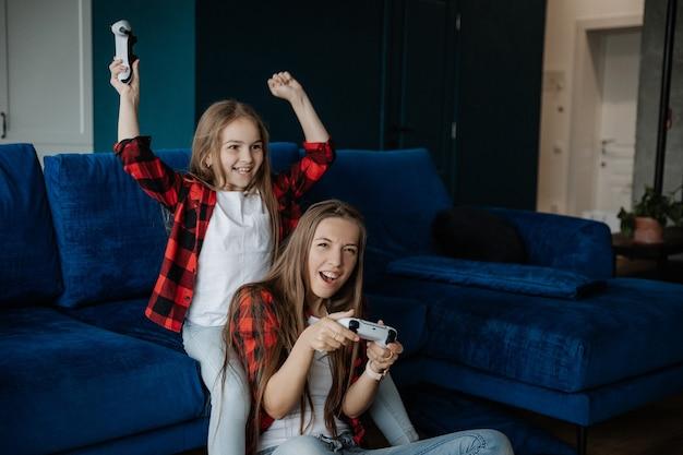 Twee meisjes hebben plezier en spelen een console met een joystick jonge zus win