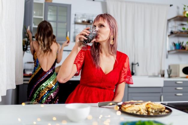 Twee meisjes hebben plezier in de keuken na een feestje