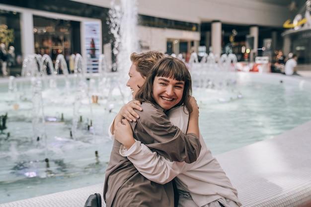 Twee meisjes hebben plezier in het winkelcentrum, naast een fontein