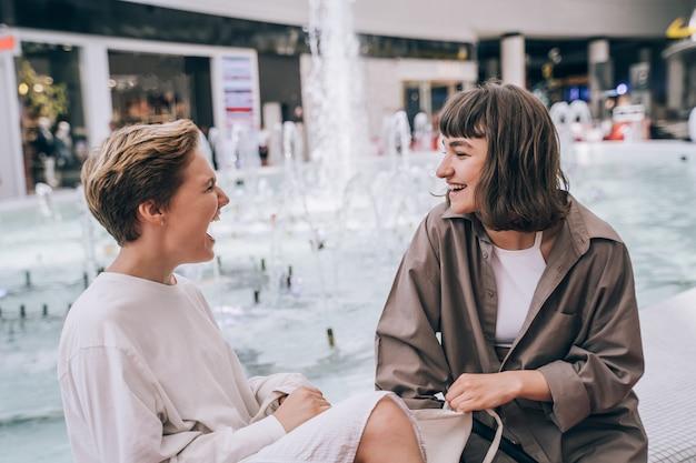 Twee meisjes hebben plezier in het winkelcentrum