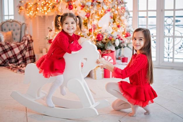 Twee meisjes hebben plezier met het berijden van een speelgoedpaard voor een kerstboom